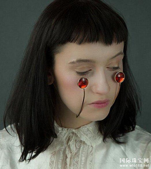 """亚纪子的作品可分为两部分:一部分是以小丑的脸部彩绘为理念,把珠宝""""架""""在脸上作为装饰。例如在眼睛上架上两块蓝宝石,鼻尖上顶一个粉宝石,再在脸颊上""""悬""""两块红宝石来代替腮红。另一部分则是用皮革制品""""替代""""原本的五官。这些饰品以黄铜丝为框架,附上各种绘制好的五官,能让使用者轻松""""整容"""",例如价值600英镑(约合人民币6000元)的带镜片眼睛。此外还有鼻子、耳朵等""""图案""""可供挑选。"""